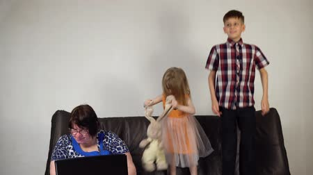 desobediente : Happy brother and sister jumping on the couch in the room. The grandmother sits next to the children and tries to work behind the laptop. Vídeos