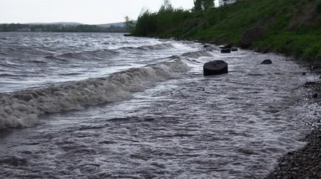 driftwood : Large waves are washed by dark stumps on the shore of the reservoir. Plastic debris and branches swim near, slow-motion shooting. Stock Footage