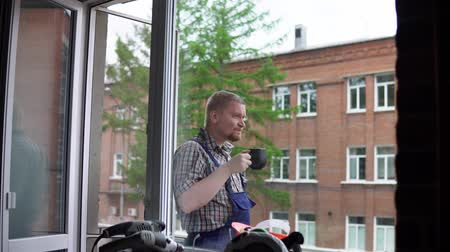 мастер на все руки : A young male working man drinks a hot drink from a black mug on a brick building background, view through a window.