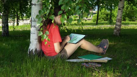 dark green : Portrait of young woman drawing pencil in the park. Dark-haired girl painting outdoor. Rest on summer weekend, holiday concept.