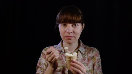 fagylalt : Young woman is eating ice cream with a spoon from a waffle cup on a black background.