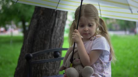 rainy day : A little girl with a toy rabbit sits on a bench, she hides from the rain under an umbrella, slow-motion.