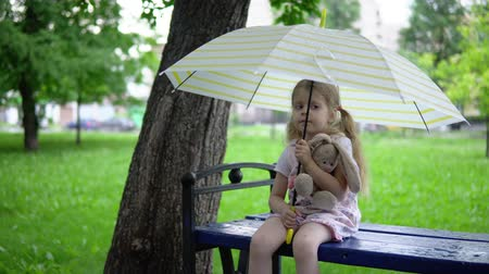 hare : A little girl with a toy rabbit sits on a bench, she hides from the rain under an umbrella.