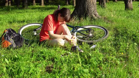 blood sport : A young woman experiences pain in the knee joint, she blows on the bleeding leg wound after riding a bicycle. The girl is very hurt, the tourist is swinging sitting in the grass in the forest.