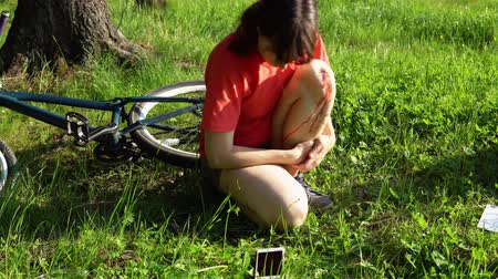 bleeding : A young woman experiences pain in the knee joint, she blows on the bleeding leg wound after riding a bicycle. The girl is very hurt, the tourist is swinging sitting in the grass in the forest.