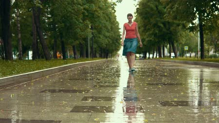 szandál : A young happy woman in blue sandals walks by the wet path in the park during the rain. Yellow leaves fall from branches of trees.