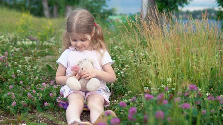 egyetlen virág : A little pretty girl plays with a plush rabbit, she sits in a meadow among a flowering clover. The child shows a pink heart.