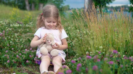 egyetlen virág : A little pretty girl plays with a plush rabbit, she sits in a meadow among a flowering clover. The child waves his hand.