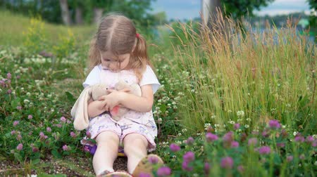 plüss : A little pretty girl plays with a plush rabbit, she sits in a meadow among a flowering clover. The child hugs and rocks the bunny.
