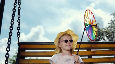 колебание : A little sweet girl in sunglasses holds a multi-colored pinwheel in her hand and swings on a swing on a warm, sunny day. Стоковые видеозаписи