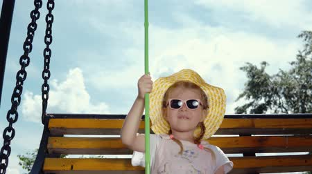 колебание : A little sweet girl in sunglasses is holding a green net in her hand and swinging on a swing on a warm, sunny day. Стоковые видеозаписи