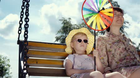колебание : Little cute girl in sunglasses and a happy young woman together swing on a swing on a warm sunny afternoon. The child holds a multi-colored pinwheel in his hand.