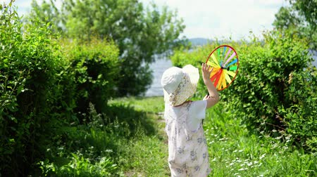 колебание : The view from the back, a little cute girl in a pink jumpsuit playing with a colorful pinwheel in the garden on a warm day.