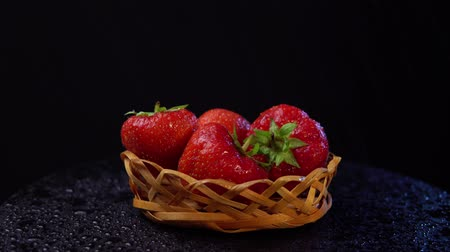 sıçramasına : Fresh, ripe juicy strawberries in a wicker basket revolve under water splashes. Red berries rotate counter-clockwise against a black background close-up. Stok Video