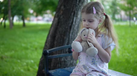 macacão : A small sad girl in a pink overalls strokes a toy bunny, a child sits on a park bench in a cloudy day.