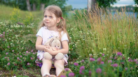 egyetlen virág : A little pretty girl plays with a plush rabbit, she sits in a meadow among a flowering clover. The child sulks and hugs the hare. Stock mozgókép