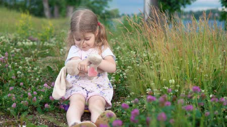 jetel : A little pretty girl plays with a plush rabbit, she sits in a meadow among a flowering clover. The child hugs and rocks the bunny.