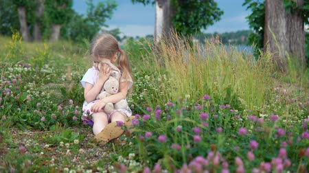 egyetlen virág : A little pretty girl plays with a plush rabbit, she sits in a meadow among a flowering clover. The child wipes his eyes with the bunnys soft ear.
