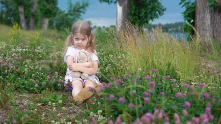 coelho : A little pretty girl plays with a plush rabbit, she sits in a meadow among a flowering clover.