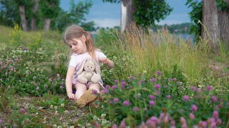 egyetlen virág : A little pretty girl plays with a plush rabbit, she sits in a meadow among a flowering clover.