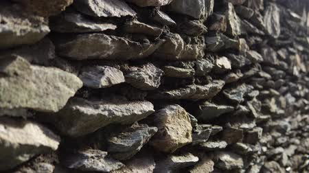 rock wall : Old granite wall with ancient stonework, abstract background. The camera moves from bottom to top. Stock Footage