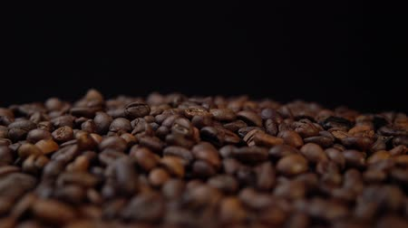 defocus : Dark roasted beans rotate counter-clockwise, side view on coffee background.