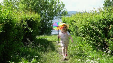 колебание : A little girl in a pink jumpsuit playing with a pinwheel, the child runs in the garden next to the river on a sunny summer day,slow motion. Стоковые видеозаписи