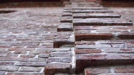 materials : Old wall with ancient crumbling brickwork, you can see the structure of the bricks. The camera is directed upwards and moves from right to left. Stock Footage