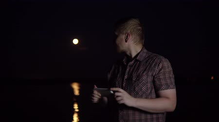 holdfény : A young man in a plaid shirt photographs a smartphones camera with a red moon over a river in a summer dark night Stock mozgókép