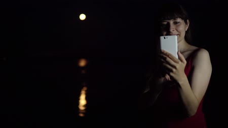 占星術 : A young woman takes a selfie using a smartphone camera against a red moon reflecting in the river, a rare astronomical phenomenon.