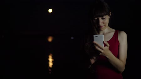 tükrözött : A young woman with dark hair uses a smartphone to photograph the view of the full moon in the sky. Red moon reflected in the river on a dark night. Stock mozgókép