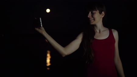 явление : A young woman makes a video call on the background of a red plenilune, a rare astronomical phenomenon. The girl smiles and waves her hand. The orange moon is reflected in the river.