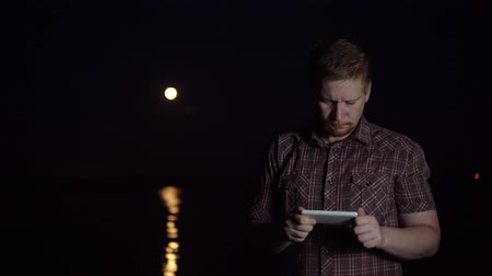 占星術 : A young man in a plaid shirt photographs a smartphones camera with a red moon over a river in a summer dark night 動画素材