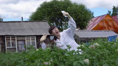 girmek : Young female scientist makes a video call using a white smartphone. A female technician in a white coat studies the growth of potato varieties on the experimental territory of the farmland.