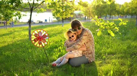 molinete : Mother and daughter in sunglasses have fun playing together on the grass under the young oaks at sunset. A young woman hugs a little girl, a child laughs.