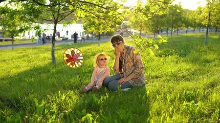 sturen : Mother and daughter in sunglasses have fun playing together on the grass under the young oaks at sunset. A young woman and a little girl send an air kiss. Stockvideo