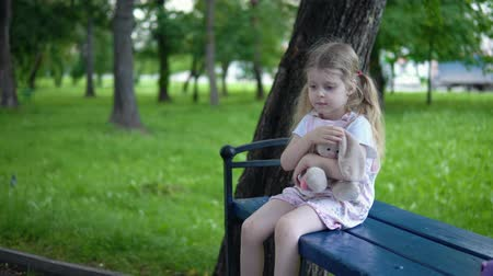 macacão : A small sad girl in a pink overalls strokes a cute toy bunny, a child sits on a park bench in a cloudy day.