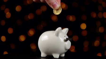 vychovávat : Piggy bank wearing a fake mustache and rotating counterclockwise against a black background with yellow lights, someone puts a coin in a money box, the concept of celebrating a movember.