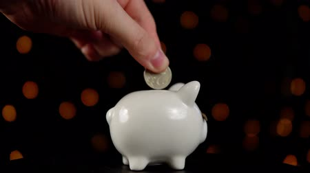 копилку : Piggy bank wearing a fake mustache and rotating counterclockwise against a black background with yellow lights, someone puts a coin in a money box, the concept of celebrating a movember.