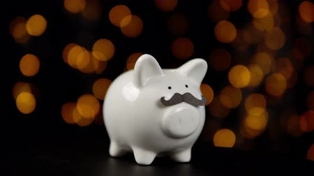 hónapokban : Piggy bank wearing a fake mustache and rotating counterclockwise against a black background with yellow lights, someone puts a coin in a money box, the concept of celebrating a movember.