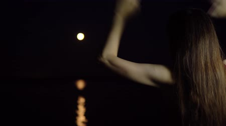 占星術 : A young woman with dark hair admires the red new moon, a rare astronomical phenomenon. The girl stands with her back to the camera on the river bank.