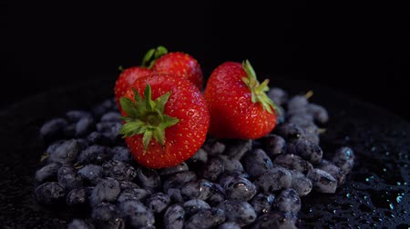 black berry : Dark honeysuckle berries and sweet strawberries rotate counter-clockwise against a black background,.