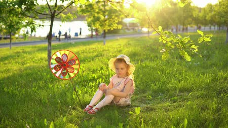 molinete : A little girl is playing with a colorful pinwheel on the grass under the young oaks in a public park at sunset Archivo de Video