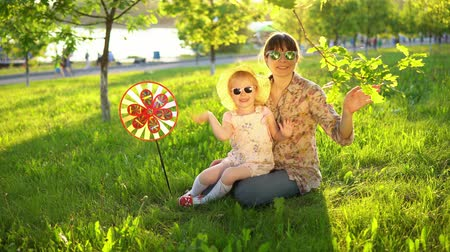 hóquei : Mother and daughter in sunglasses have fun playing together on the grass under the young oaks at sunset, they look at the camera and wave their hands, then fold the heart symbol. Stock Footage