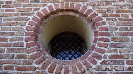 antiquado : A round window with a black forged metal grille in an old medieval restored brick building with thick walls. The camera moves from left to right.