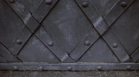 antique grunge : An old medieval restored black metal door reinforced with overlaid plates. The camera moves from left to right. Stock Footage