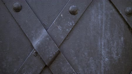 antiquado : An old medieval restored black metal door reinforced with overlaid plates. The camera moves from right to left.