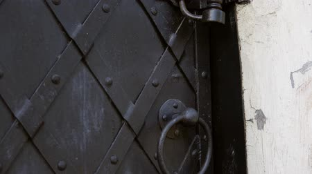 perçin : An old medieval restored black metal door reinforced with overlaid plates. Move the camera from top to bottom.