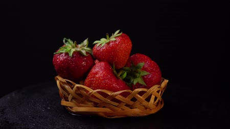 ehető : Fresh, ripe juicy strawberries in a wicker basket revolve under water splashes. Red berries rotate counter-clockwise against a black background close-up. Stock mozgókép
