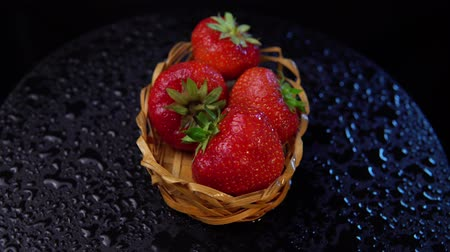 proutěný : Fresh, ripe juicy strawberries in a wicker basket revolve under water splashes. Red berries rotate counter-clockwise against a black background close-up. Dostupné videozáznamy
